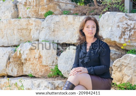 Young woman sitting outside on stones, sunlight