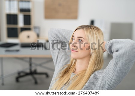 Young woman sitting thinking in the office relaxing in her chair with her hands behind her neck staring off into the air with a contemplative expression - stock photo