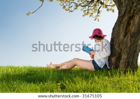 Young woman sitting under a blossom tree reads a book while wearing a lovely purple hat - stock photo