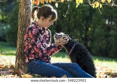 Young woman sitting under an autumn tree cuddling her black dog outside in a park. - stock photo
