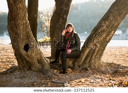 Young woman sitting under tree at autumn park next to river - stock photo