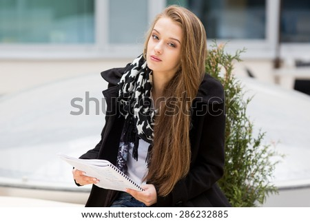 Young woman sitting with a book.  - stock photo