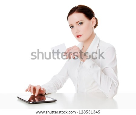 Young woman sitting with a tablet computer and holding a credit card. - stock photo