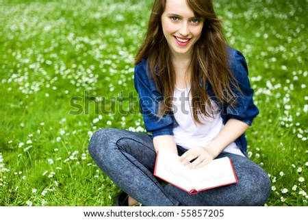 Young woman sitting with book on grass - stock photo