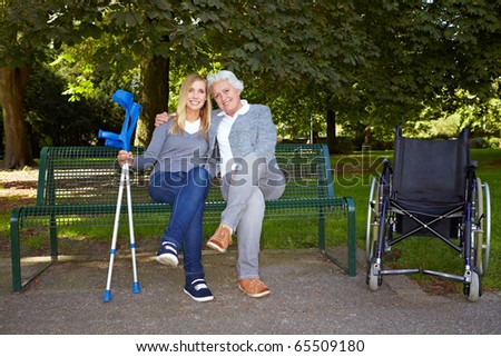 Young woman sitting with elderly handicapped woman on a park bench - stock photo