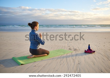 Young woman sitting with her knees bent and hands together on her yoga-mat at the beach doing yoga breathing exercises early in the morning - stock photo