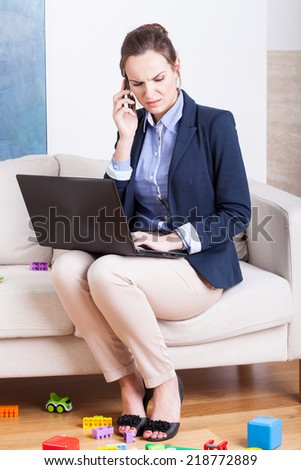 Young woman sitting with laptop and phone and toys on floor - stock photo