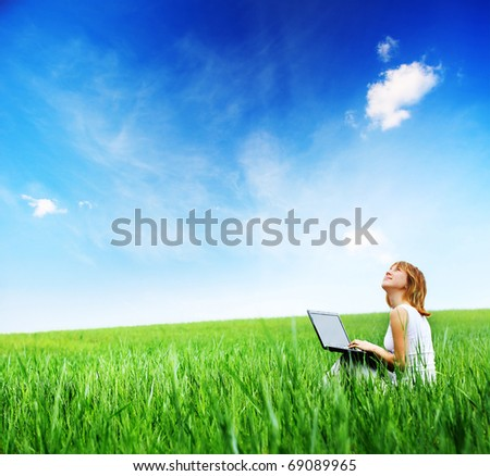 Young woman sitting with laptop on a green meadow - stock photo