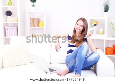 Young woman sitting with laptop on sofa and holding credit card in her hand, at home - stock photo