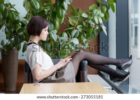 Young woman sitting with tablet pc and working. - stock photo
