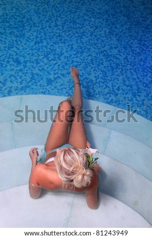 Young woman sittingin in a swimming pool  at spa resort - stock photo