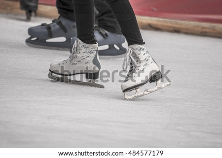 Young woman skating on ice. Ice skates as a detail,