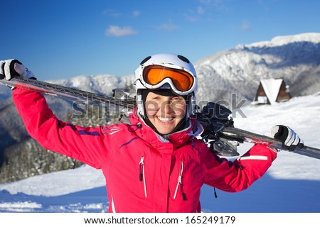 Young woman ski goggles and a helmet holding ski in the mountains