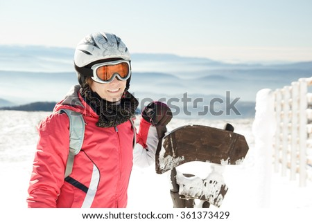 Young woman skier at winter ski resort in mountains
