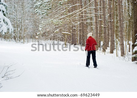 Young woman skiing in through winter forest - stock photo