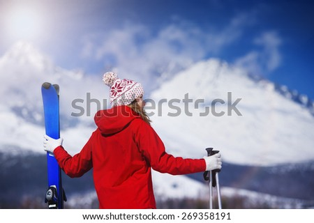 Young woman skiing outside in sunny winter mountains - stock photo