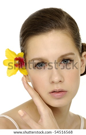 Young woman skin of her face with a yellow orchid from her ear
