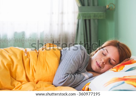 Young woman sleeping in bed - stock photo