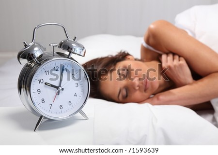 Young woman sleeping in bed with alarm clock in foreground - stock photo