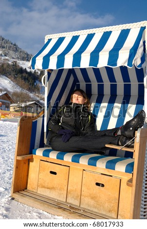 Young woman sleeping in roofed wicker beach chair on a sunny winter day in austria. - stock photo