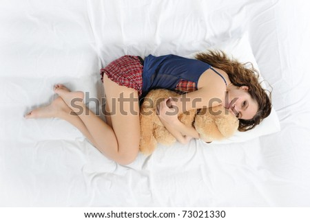 Young woman sleeping on a bed in an embrace with teddybear - stock photo