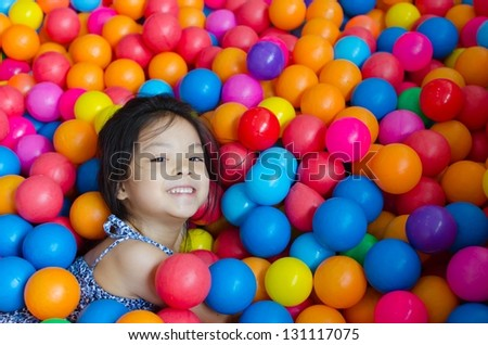 Young woman sleeping on ball many colors.