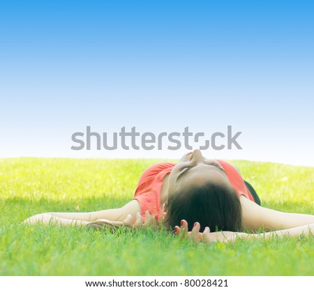 Young woman sleeping on green grass with space for text.