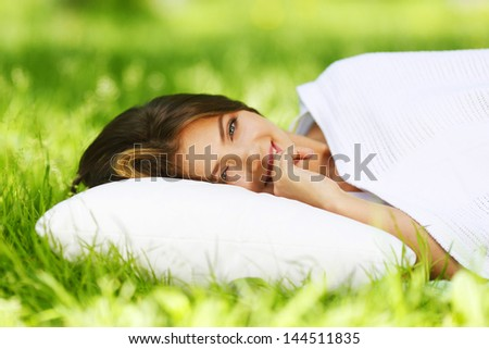 Young woman sleeping on soft pillow in fresh spring grass - stock photo