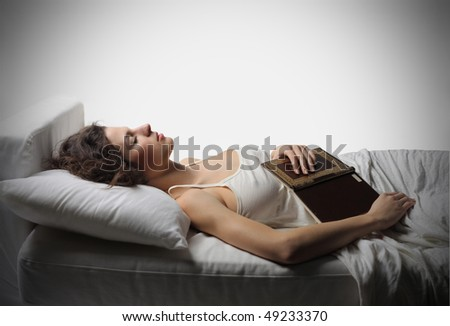 Young woman sleeping with a book in her hands - stock photo
