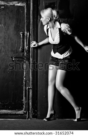 Young woman slinking to the door. Black and white high contrast colors. - stock photo