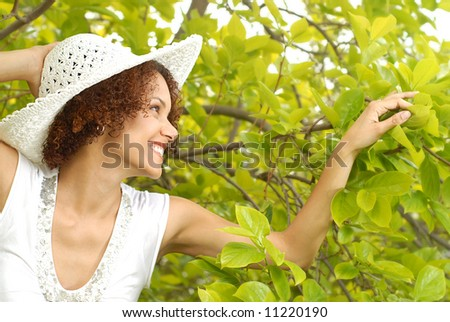 Young woman slowly walking through a lush garden on a beautiful spring day