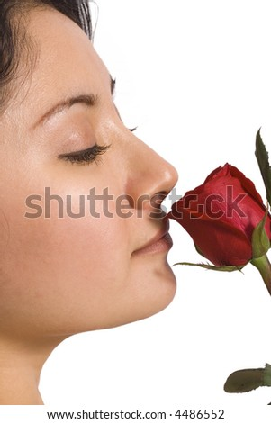 Young woman smelling a beautiful red rose