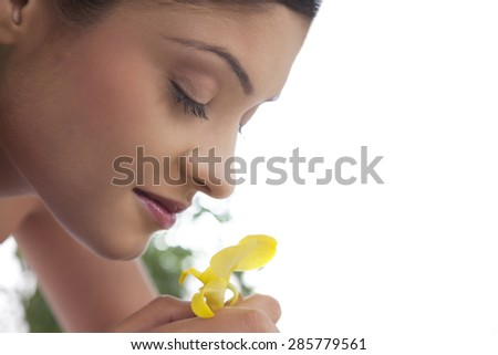 Young woman smelling flower - stock photo