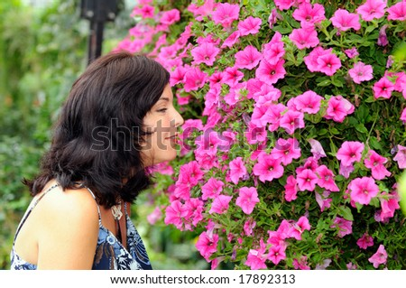 Young Woman Smelling Flower Blooms - stock photo