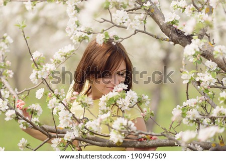 young woman smelling flowers on branch - stock photo
