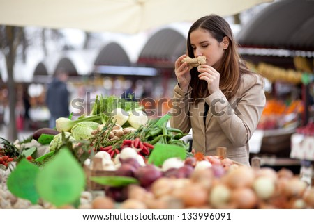 Young woman smelling ginger at the market