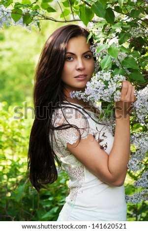 Young woman smelling lilac in spring park