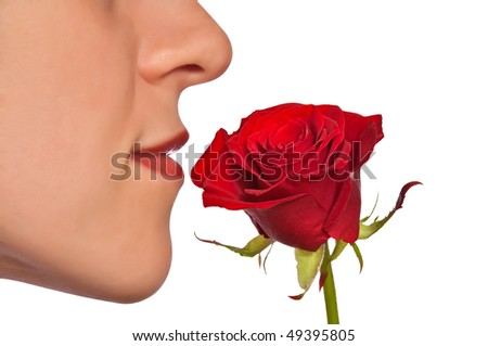 Young woman smelling red rose
