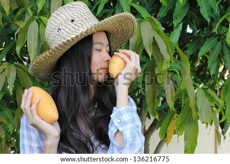 Young woman smelling ripe mango - stock photo