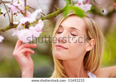 Young woman smelling the blossoms on a cherry tree