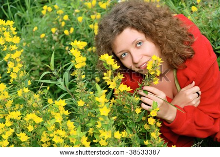 Young woman smelling yellow flowers in garden - stock photo