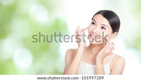 Young woman smile and hand touch face look to up forward concept for health body care with green nature background, model is a asian beauty - stock photo