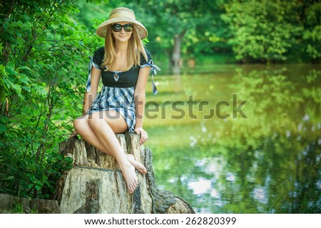 Young woman smiles in black glasses and hat on stub, in summer city park. - stock photo