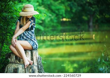 Young woman smiles in straw hat on stub, in summer city park.
