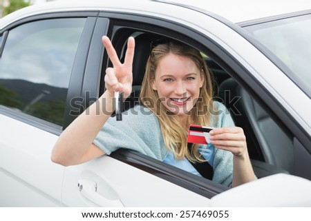 Young woman smiling and holding card in her car - stock photo