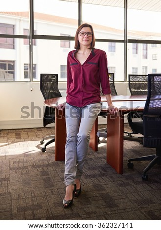 Young woman smiling and looking like a relaxed and confident business leader while sitting on the edge of her desk in an office with large windows - stock photo
