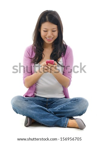 Young Woman smiling and texting on her mobile phone, sitting isolated over white background.  - stock photo