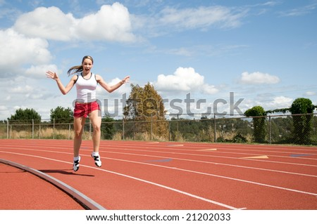 Young woman smiling as she jumps on a track. Horizontally framed photo.