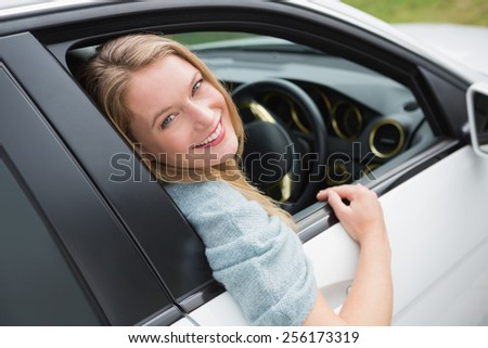 Young woman smiling at camera in her car