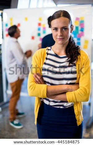Young woman smiling at camera while her colleagues discussing in the background - stock photo